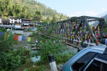 Prayer flag covered bridge at the start of the trek